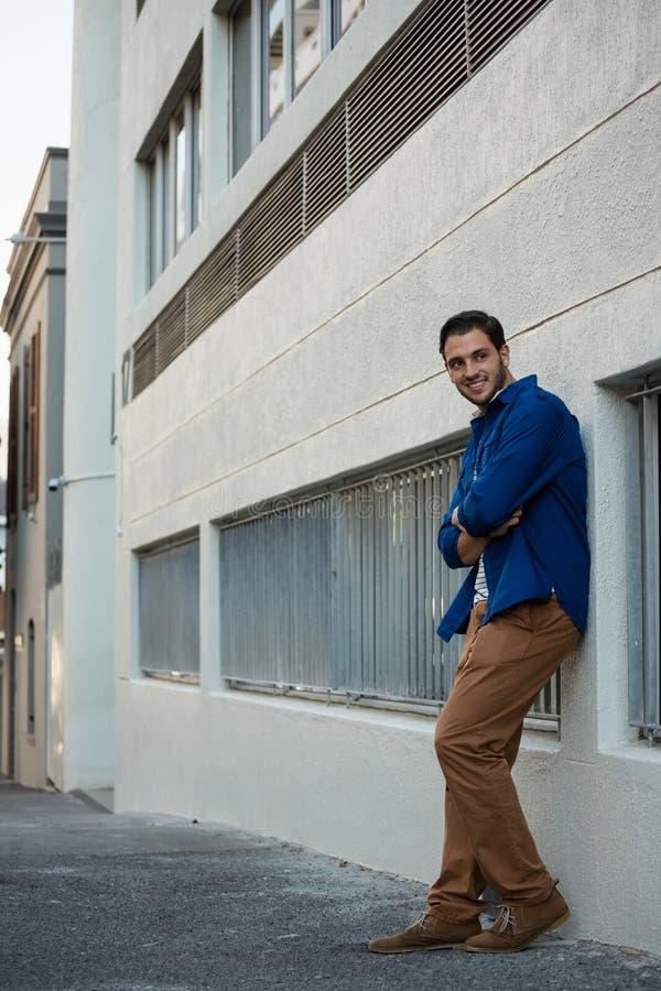 Χαμογελώντας άτομο με τα όπλα που διασχίζονται κλίση στον τοίχο στοκ φωτογραφίες με δικαίωμα ελεύθερης χρήσης