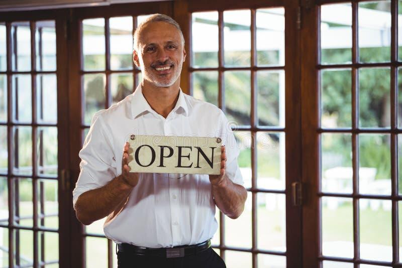 Χαμογελώντας άτομο που κρατά ένα σημάδι με ανοικτό στοκ φωτογραφίες
