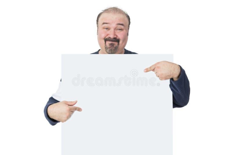 Χαμογελώντας άτομο που κρατά και που δείχνει έναν πίνακα διαφημίσεων στοκ φωτογραφία με δικαίωμα ελεύθερης χρήσης