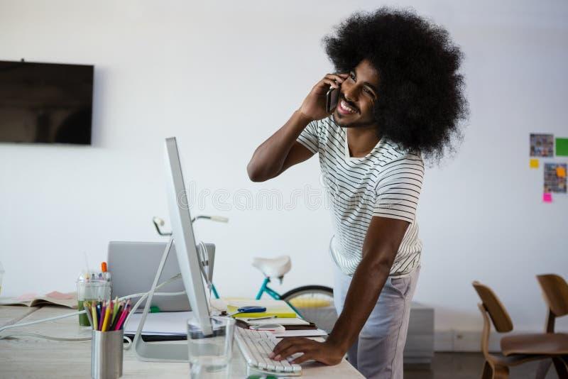 Χαμογελώντας άτομο που μιλά στο τηλέφωνο χρησιμοποιώντας τον υπολογιστή στην αρχή στοκ εικόνα