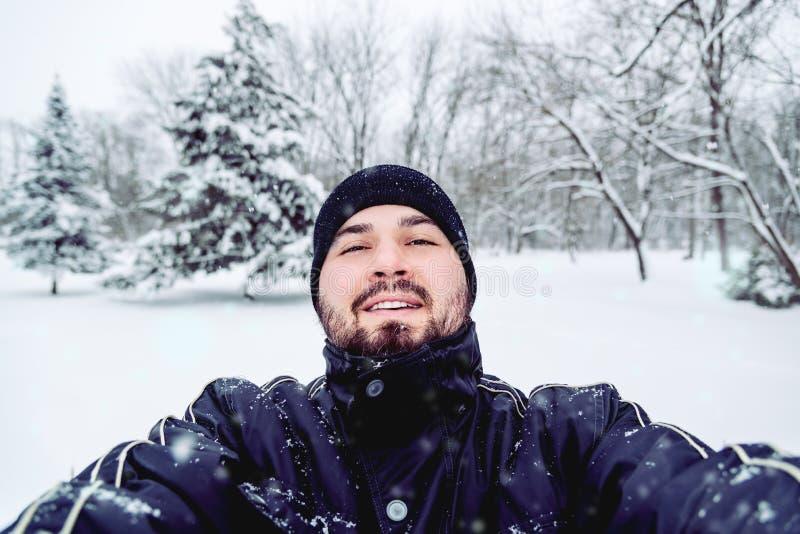 Χαμογελώντας άτομο που παίρνει Selfie στη θύελλα χιονιού στοκ φωτογραφίες