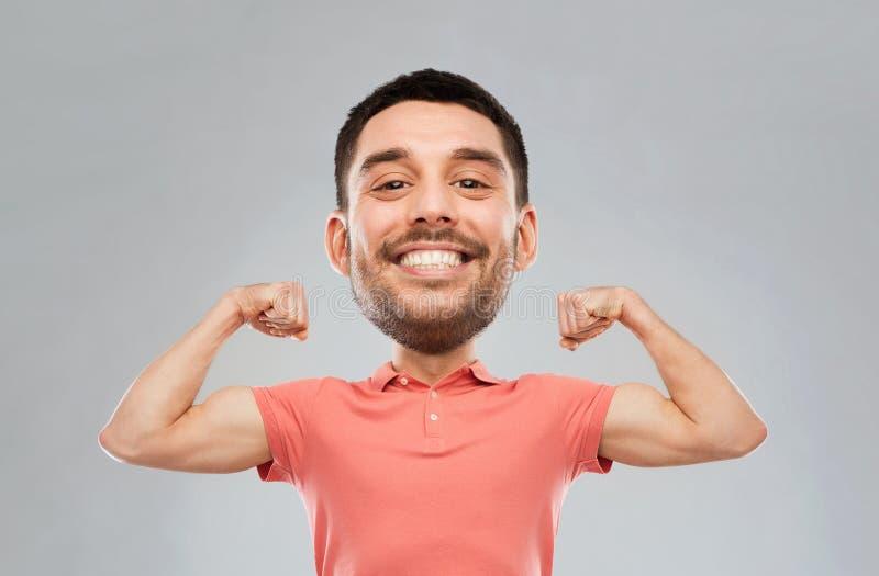 Χαμογελώντας άτομο που παρουσιάζει δικέφαλους μυς πέρα από το γκρίζο υπόβαθρο στοκ φωτογραφίες με δικαίωμα ελεύθερης χρήσης