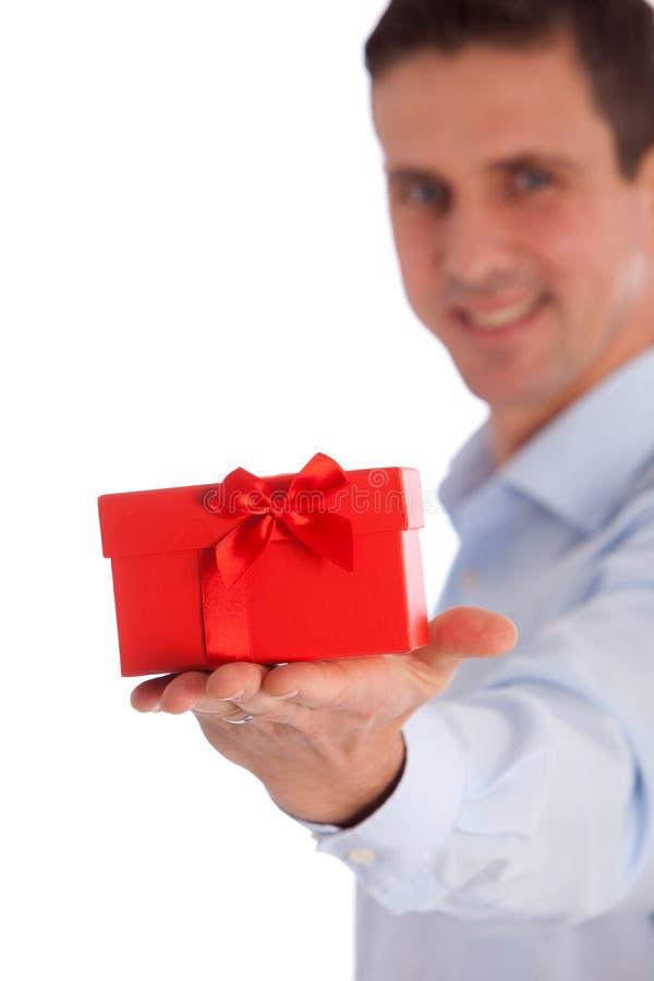 Χαμογελώντας άτομο που προσφέρει ένα δώρο σε ένα κόκκινα κιβώτιο και ένα τόξο στοκ εικόνες