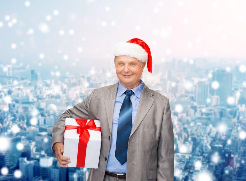 Χαμογελώντας άτομο στο καπέλο αρωγών κοστουμιών και santa με το δώρο στοκ φωτογραφίες