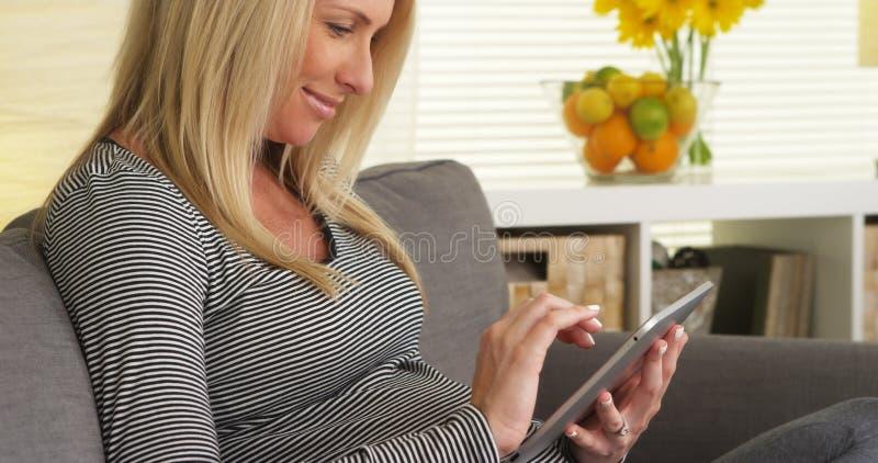 Χαμογελώντας έγκυος γυναίκα που χρησιμοποιεί την ταμπλέτα στοκ φωτογραφίες