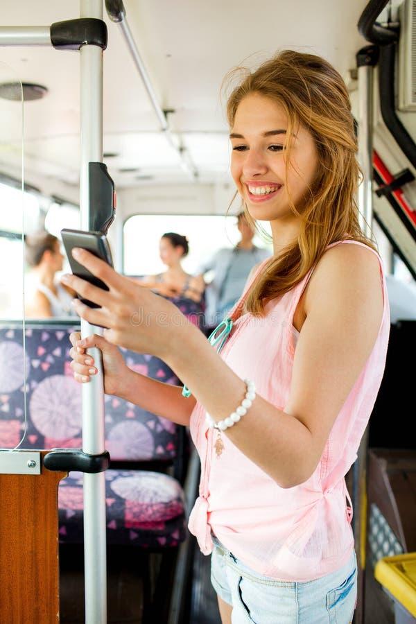 Χαμογελώντας έφηβη με το smartphone που πηγαίνει με το λεωφορείο στοκ εικόνες