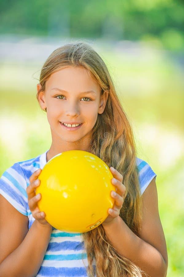 Χαμογελώντας έφηβη που κρατά την κίτρινη σφαίρα στοκ φωτογραφία