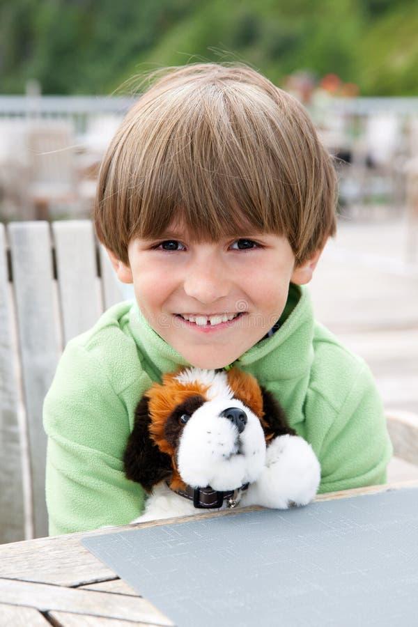 Χαμογελώντας αγόρι με ένα αγαπημένο μαλακό παιχνίδι στοκ εικόνες