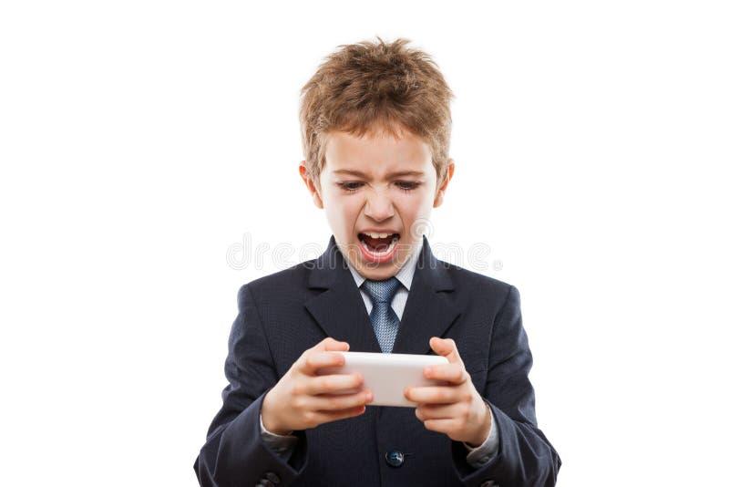 Χαμογελώντας αγόρι παιδιών στα παίζοντας παιχνίδια επιχειρησιακών κοστουμιών ή κάνοντας σερφ Διαδίκτυο στον υπολογιστή smartphone στοκ εικόνα