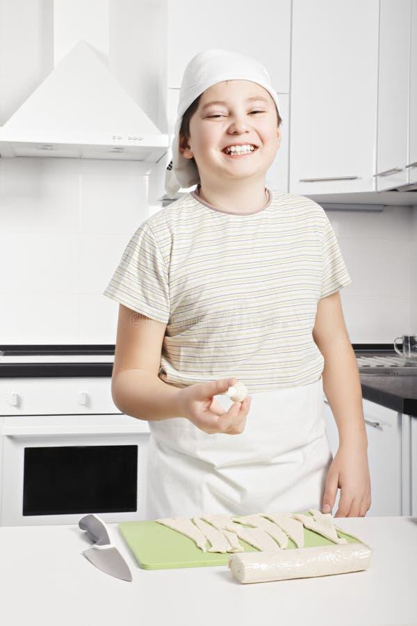 Χαμογελώντας αγόρι που κρατά ακατέργαστο croissant στοκ εικόνα