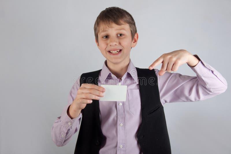 Χαμογελώντας αγόρι που κρατά την άσπρη τραπεζική κάρτα και που παρουσιάζει σε την από το δάχτυλο στοκ φωτογραφία με δικαίωμα ελεύθερης χρήσης
