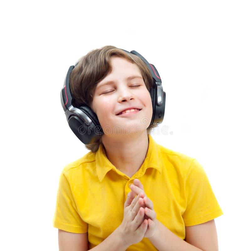 Χαμογελώντας αγόρι στη μουσική ακούσματος ακουστικών στοκ εικόνες με δικαίωμα ελεύθερης χρήσης