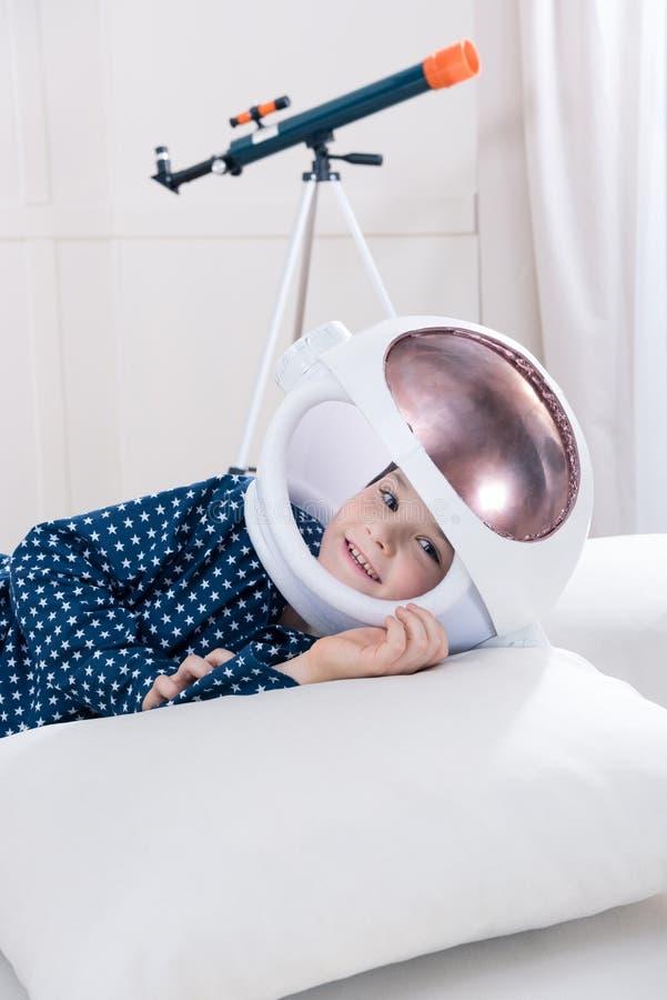 Χαμογελώντας αγόρι στις πυτζάμες και το διαστημικό κράνος που βρίσκονται στο μαξιλάρι στοκ εικόνες