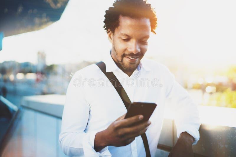 Χαμογελώντας αμερικανικό αφρικανικό άτομο που χρησιμοποιεί το smartphone για να καλέσει τους φίλους του στην ηλιόλουστη πόλη ενώ  στοκ εικόνα με δικαίωμα ελεύθερης χρήσης