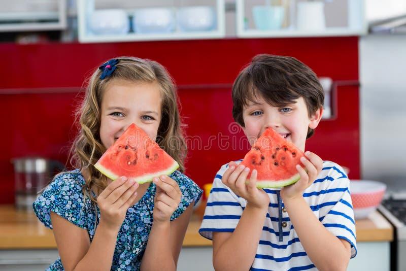Χαμογελώντας αμφιθαλείς που έχουν το καρπούζι στην κουζίνα στοκ φωτογραφία με δικαίωμα ελεύθερης χρήσης