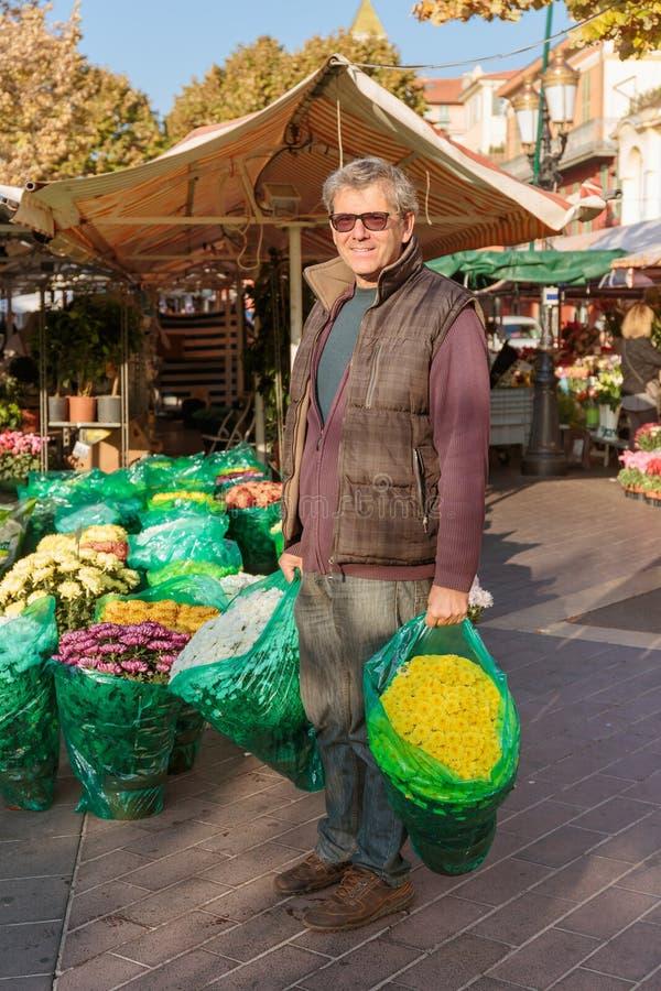 Χαμογελώντας ανθοκόμος πωλητών στο ανθοπωλείο στη Νίκαια, Γαλλία στοκ φωτογραφία