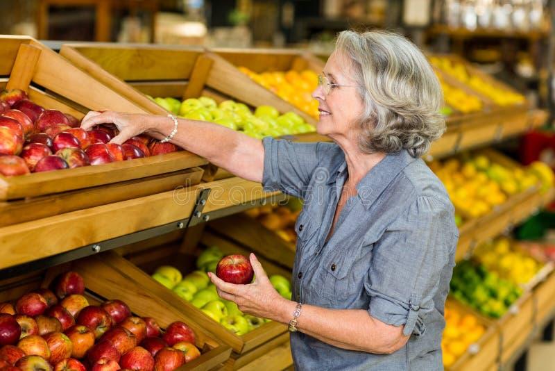 Χαμογελώντας ανώτερα μήλα επιλογής γυναικών στοκ εικόνα