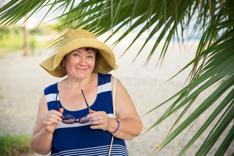 Χαμογελώντας ανώτερη γυναίκα που φορά το καπέλο κάτω από τους φοίνικες στοκ φωτογραφία