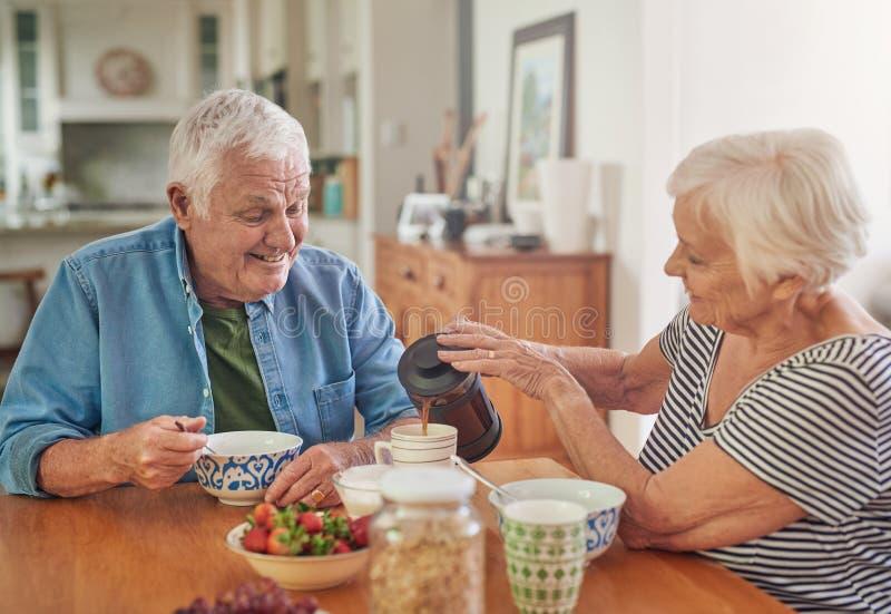Χαμογελώντας ανώτερη γυναίκα που χύνει στο σύζυγό της έναν καφέ πέρα από το πρόγευμα στοκ φωτογραφία