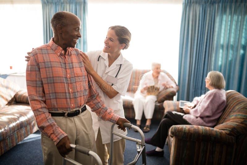 Χαμογελώντας ανώτερο άτομο με τον περιπατητή που εξετάζει το θηλυκό γιατρό ενάντια στο παράθυρο στοκ εικόνες