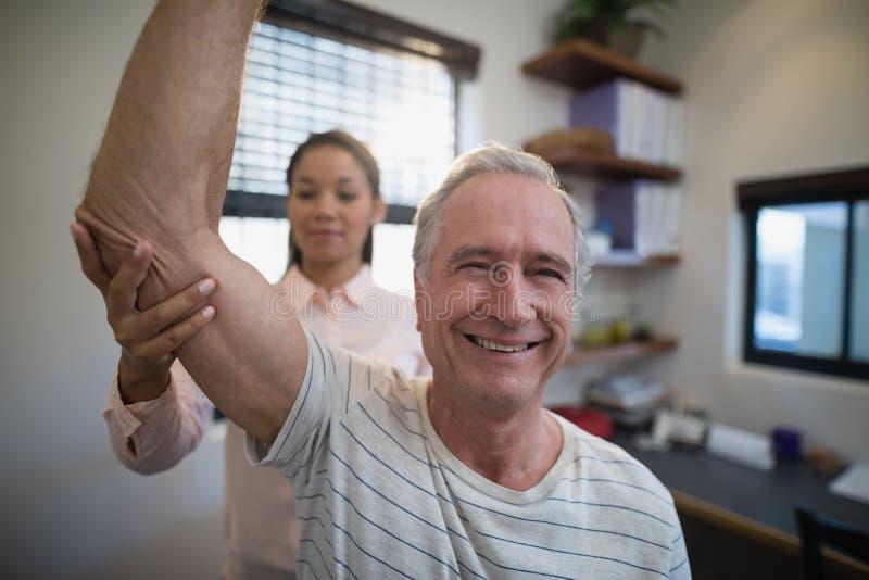 Χαμογελώντας ανώτερο άτομο που κοιτάζει μακριά ενώ θηλυκός γιατρός που εξετάζει τον αγκώνα στοκ φωτογραφία με δικαίωμα ελεύθερης χρήσης