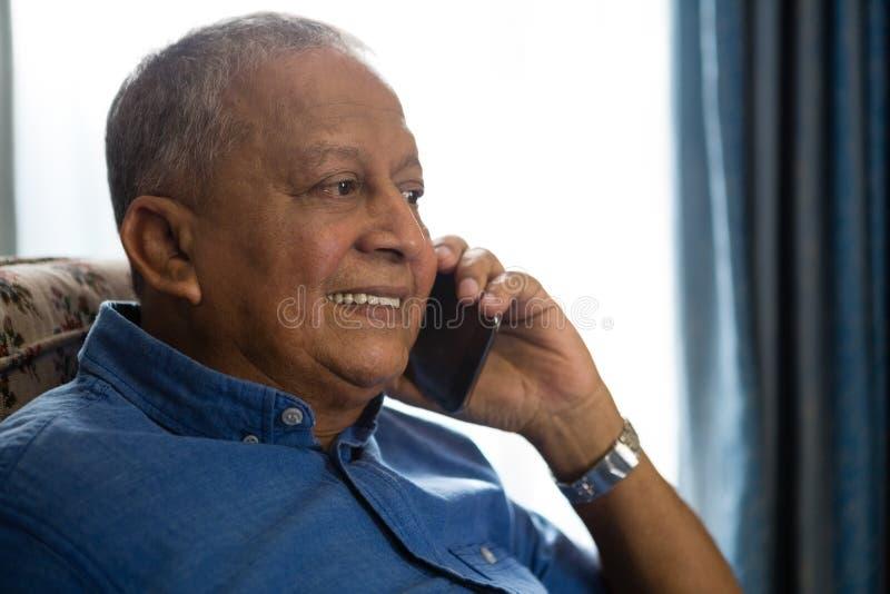 Χαμογελώντας ανώτερο άτομο που μιλά στο κινητό τηλέφωνο στη ιδιωτική κλινική στοκ εικόνες