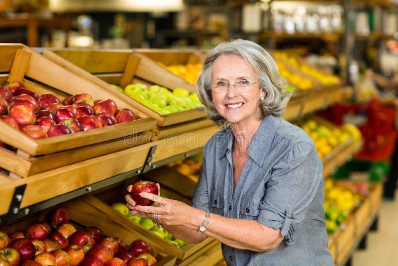 Χαμογελώντας ανώτερο μήλο επιλογής γυναικών στοκ φωτογραφία
