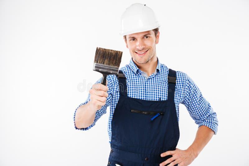 Χαμογελώντας αρσενική βούρτσα χρωμάτων εκμετάλλευσης ζωγράφων στοκ φωτογραφία