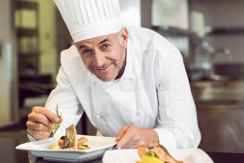 Χαμογελώντας αρσενικός αρχιμάγειρας που διακοσμεί τα τρόφιμα στην κουζίνα στοκ φωτογραφία με δικαίωμα ελεύθερης χρήσης