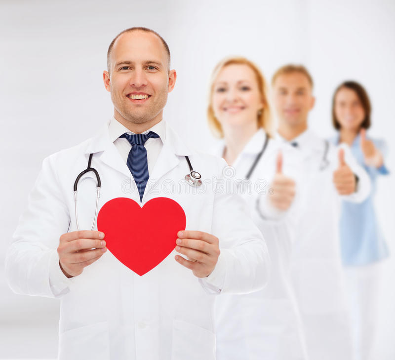 Χαμογελώντας αρσενικός γιατρός με την κόκκινα καρδιά και το στηθοσκόπιο στοκ εικόνες
