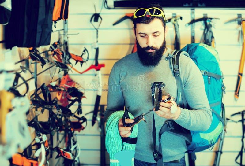Χαμογελώντας αρσενικός πελάτης που εξετάζει αναρριμένος στον εξοπλισμό στο αθλητικό equ στοκ φωτογραφία με δικαίωμα ελεύθερης χρήσης