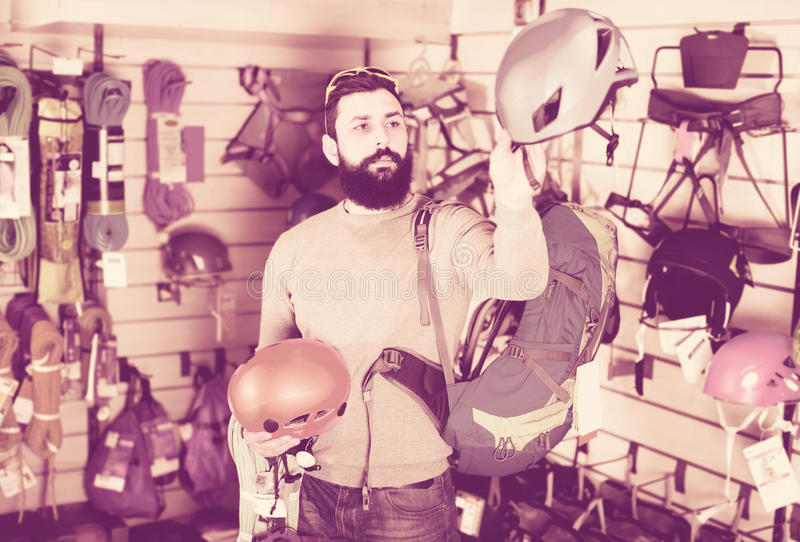 Χαμογελώντας αρσενικός πελάτης που εξετάζει τα κράνη στο stor αθλητικού εξοπλισμού στοκ εικόνες