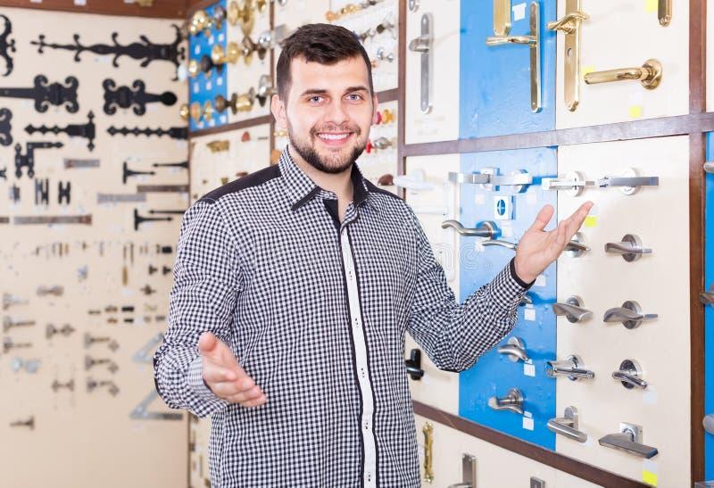 Χαμογελώντας αρσενικός πελάτης που εξετάζει τις διάφορες λαβές πορτών στο κατάστημα στοκ φωτογραφία με δικαίωμα ελεύθερης χρήσης