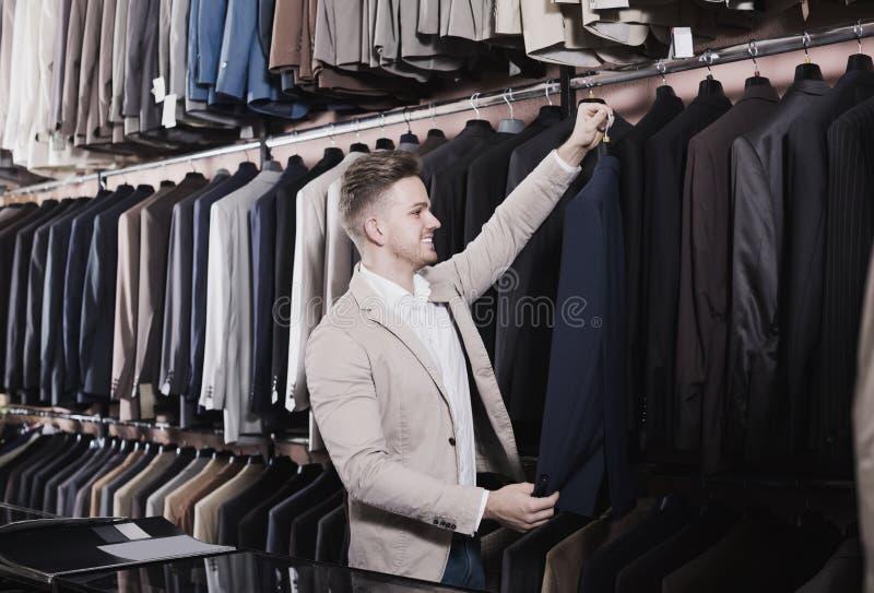 Χαμογελώντας αρσενικός πελάτης που εξετάζει men's τα κοστούμια στοκ εικόνα με δικαίωμα ελεύθερης χρήσης