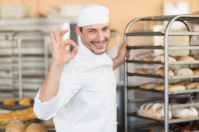 Χαμογελώντας αρτοποιός που κάνει το εντάξει σημάδι με το χέρι στοκ εικόνες