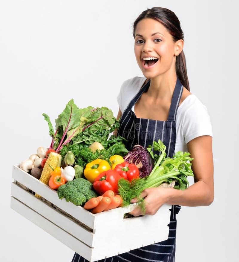 Χαμογελώντας αρχιμάγειρας με την ποδιά που κρατά τα φρέσκα τοπικά οργανικά προϊόντα στοκ φωτογραφία