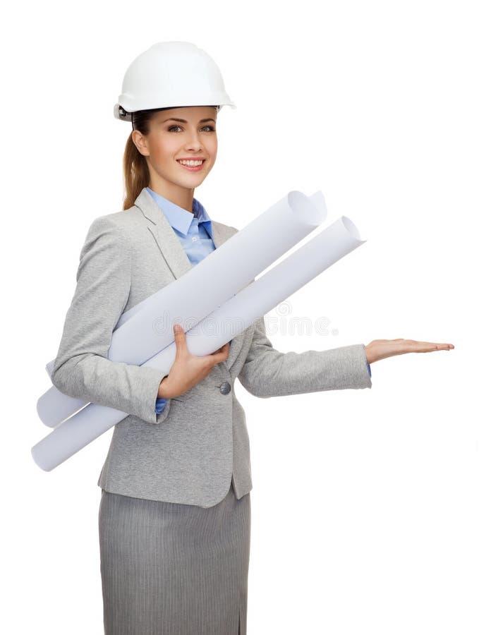 Χαμογελώντας αρχιτέκτονας στο άσπρο κράνος με τα σχεδιαγράμματα στοκ εικόνες