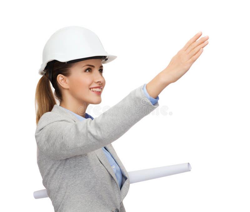 Χαμογελώντας αρχιτέκτονας στο άσπρο κράνος με τα σχεδιαγράμματα στοκ εικόνες με δικαίωμα ελεύθερης χρήσης