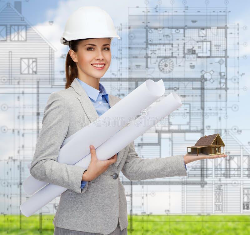 Χαμογελώντας αρχιτέκτονας στο άσπρο κράνος με τα σχεδιαγράμματα στοκ εικόνα