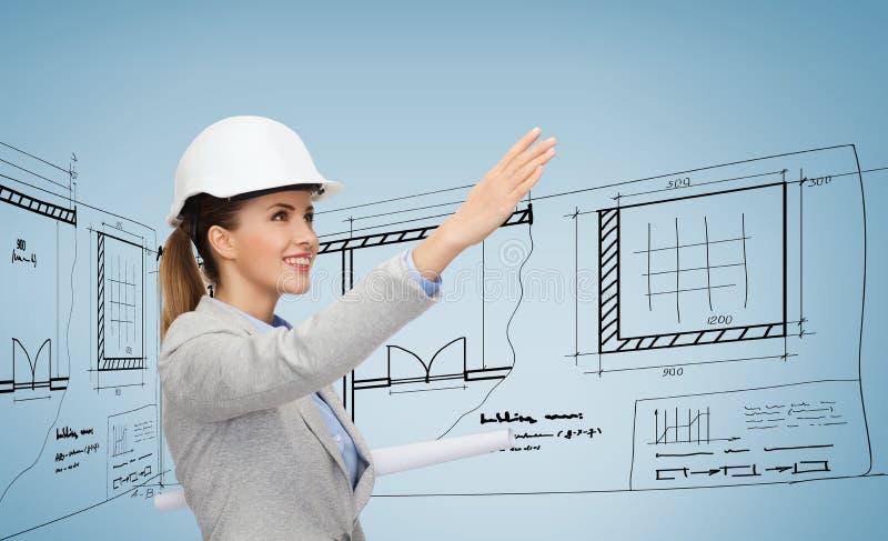 Χαμογελώντας αρχιτέκτονας στο άσπρο κράνος με τα σχεδιαγράμματα στοκ φωτογραφίες