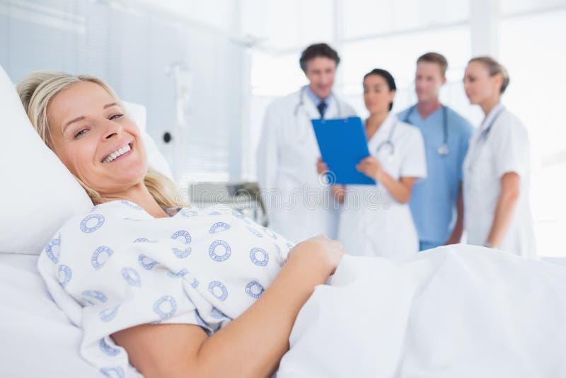 Χαμογελώντας ασθενής που εξετάζει τη κάμερα με τους γιατρούς πίσω στοκ εικόνες με δικαίωμα ελεύθερης χρήσης