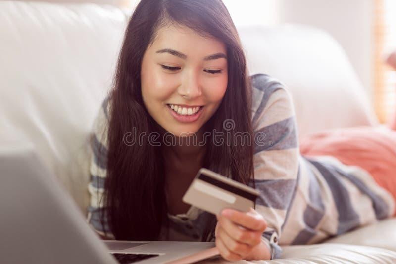 Χαμογελώντας ασιατική γυναίκα στον καναπέ που χρησιμοποιεί την ταμπλέτα για να ψωνίσει on-line στοκ φωτογραφία