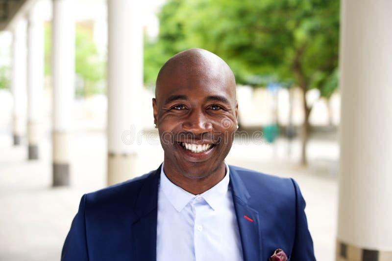 Χαμογελώντας αφρικανικός επιχειρηματίας που στέκεται υπαίθρια στοκ εικόνες