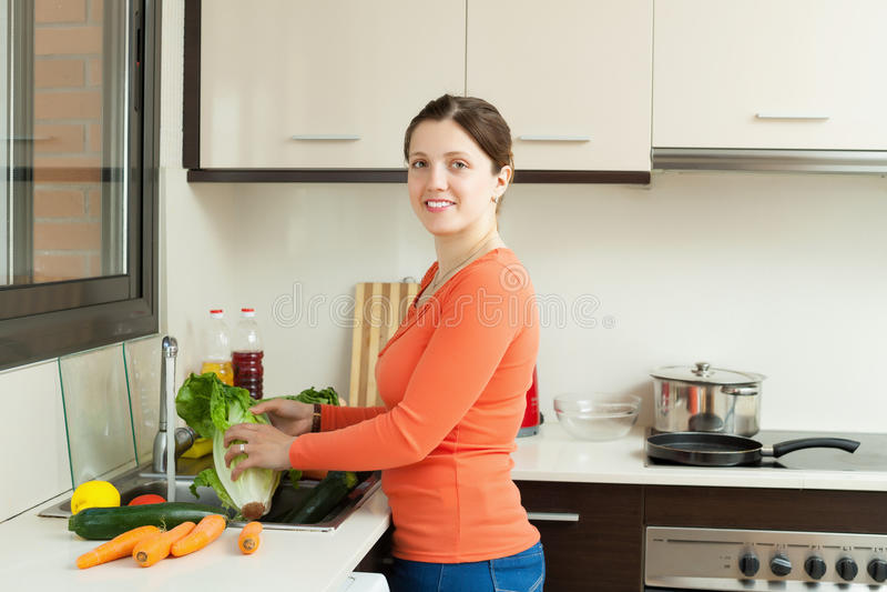 Χαμογελώντας λαχανικά πλύσης νοικοκυρών στοκ φωτογραφίες με δικαίωμα ελεύθερης χρήσης