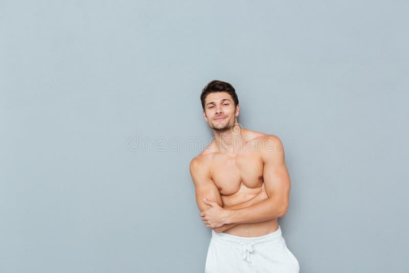 Χαμογελώντας βέβαιος νεαρός άνδρας γυμνοστήθων που στέκεται με τα όπλα που διασχίζονται στοκ εικόνες