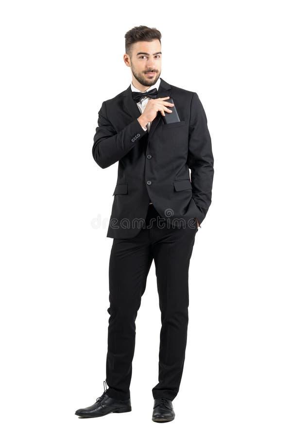 Χαμογελώντας βέβαιο πολυτελές άτομο στο κοστούμι που βάζει το κινητό τηλέφωνο στην τσέπη κοστουμιών που εξετάζει τη κάμερα στοκ φωτογραφίες με δικαίωμα ελεύθερης χρήσης