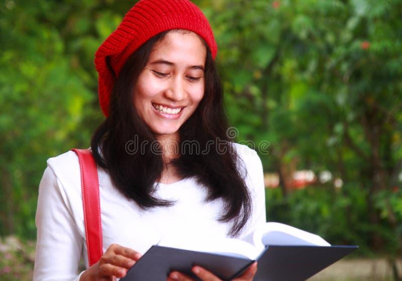 Χαμογελώντας βιβλίο ανάγνωσης γυναικών σπουδαστών στοκ φωτογραφία με δικαίωμα ελεύθερης χρήσης
