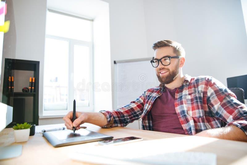 Χαμογελώντας γενειοφόρος σχεδιαστής που σύρει και που χρησιμοποιεί τη γραφική ταμπλέτα μανδρών στοκ φωτογραφία