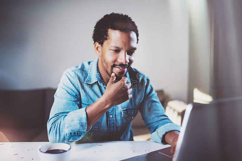 Χαμογελώντας γενειοφόρο αφρικανικό άτομο που εργάζεται στο lap-top ξοδεύοντας το χρόνο το δωμάτιο Έννοια των νέων επιχειρηματιών στοκ εικόνες