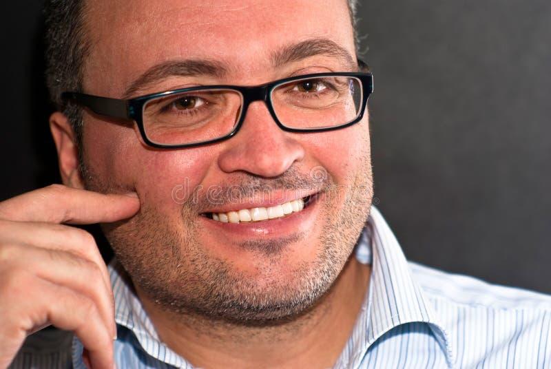 Χαμογελώντας γενειοφόρο καυκάσιο άτομο που φορά eyeglasses το ριγωτό πουκάμισο στοκ εικόνα με δικαίωμα ελεύθερης χρήσης